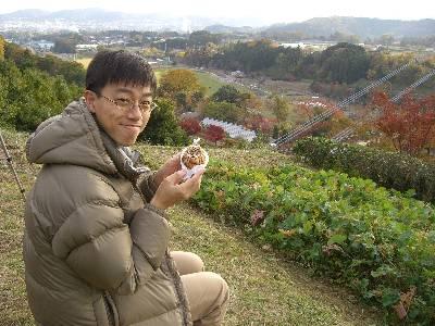 広大な風景を見ながらパンを食べる奥村