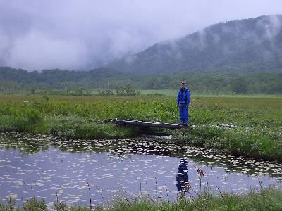 池にかかる小さな橋に佇む奥村
