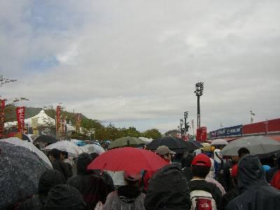 傘をさす人々で混雑する C 席裏の売店の列の間の通路