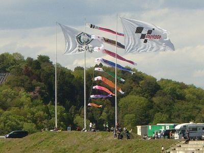 強風になびく旗と鯉のぼり