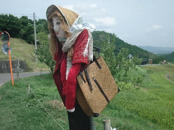 本物のバッグを持つ案山子