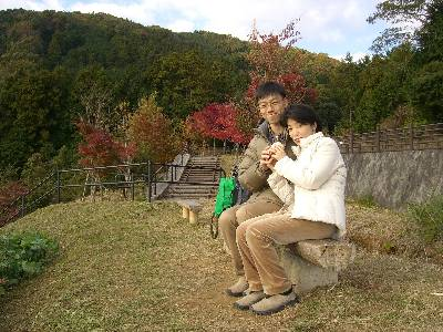 ベンチでパンを食べる奥村と妻