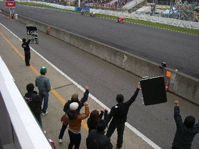 GP-250 決勝、関口選手にサインボードを出すクルーと、応援する関係者